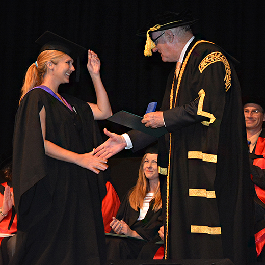 Biomedical Science graduate Cat Manwaring receives her University Medal from Chancellor John Dobson