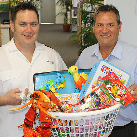 USC Senior HR Consultant (Health, Safety and Wellbeing) Peter Gooding presenting the hampers to Salvation Army Maroochydore officer Daniel Ross (left).