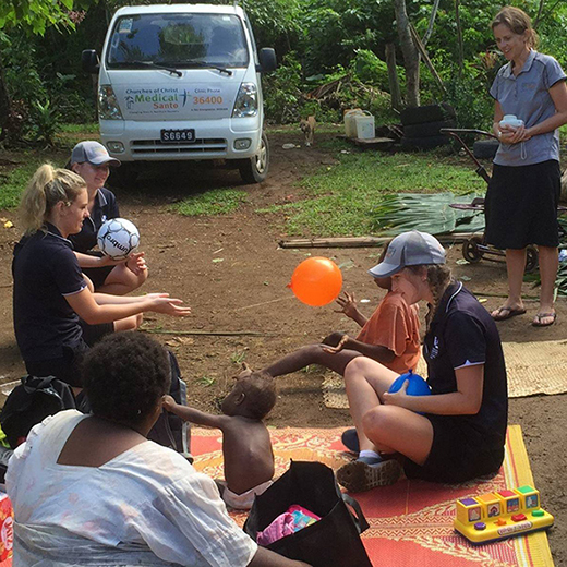 USC students and Dr Kennedy-Behr working with a child in Vanuatu in 2016.