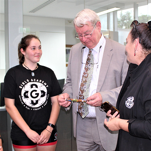 Members of members of the Urangan State High School's Girls Academy present a message stick to USC Vice-Chancellor Professor Greg Hill.