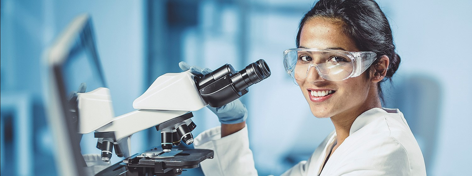 female lab researcher at microscope looking at camera